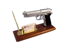 Pistol mounted on wood with card holder and pen