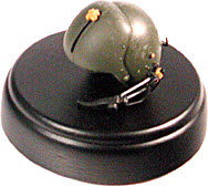 Helicopter pilot helmet on round black wood base