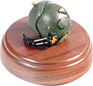 Helicopter pilot helmet on round walnut wood base